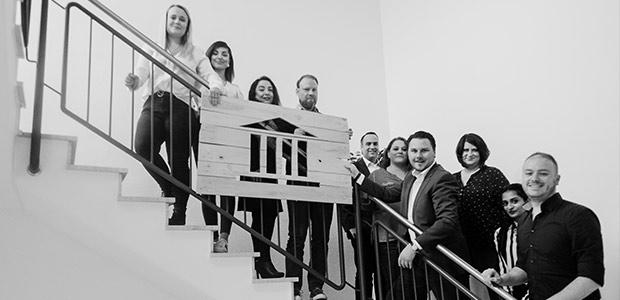 Das gesamte Team von Martin Bleckmann auf einer Treppe