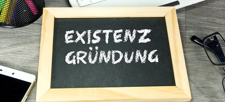 Ein Büro und eine Kreidetafel mit dem Wort Existenzgründung als Symbol für die Hilfe bei der Existenzgründung von Martin Bleckmann