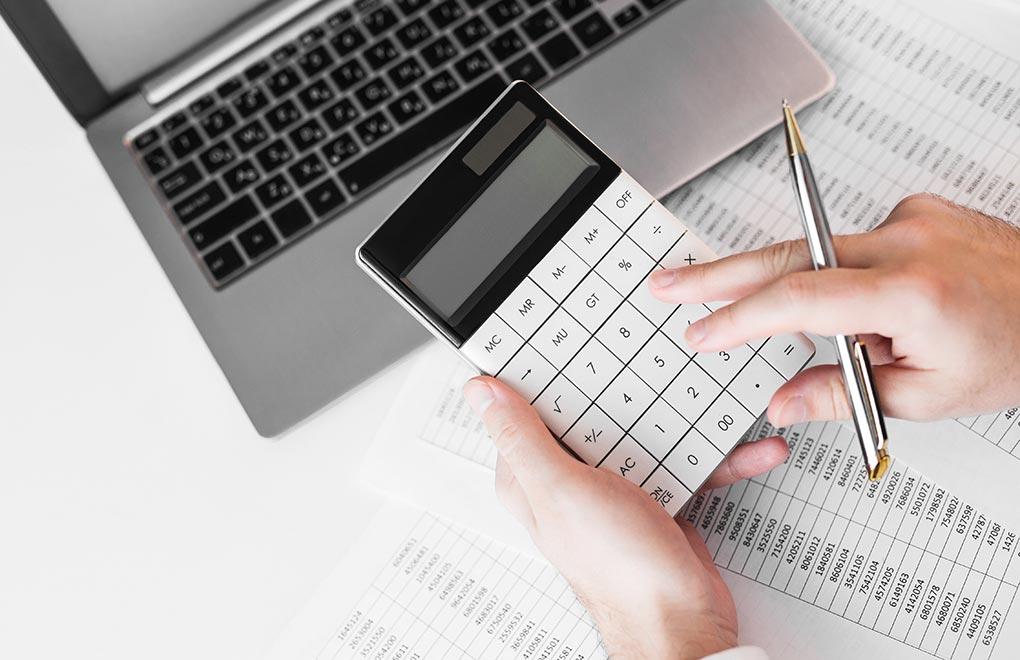 Hände tippen auf Taschenrechner als Symbol für Jahresabschlussrechnung